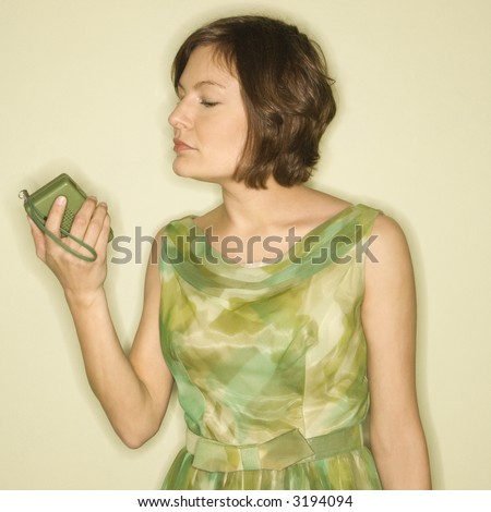 Pretty Caucasian mid-adult woman wearing green vintage dress looking at handheld radio. - stock photo