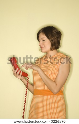 Pretty Caucasian mid-adult woman wearing orange dress standing dialing red telephone. - stock photo