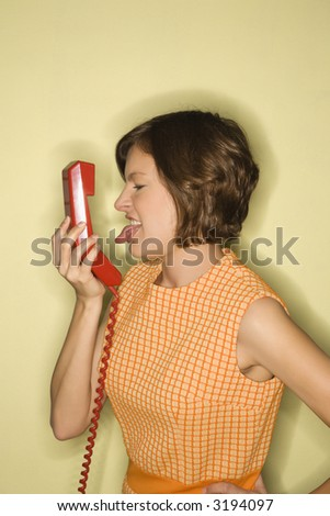 Pretty Caucasian mid-adult woman wearing orange dress sticking out tongue at red telephone receiver. - stock photo