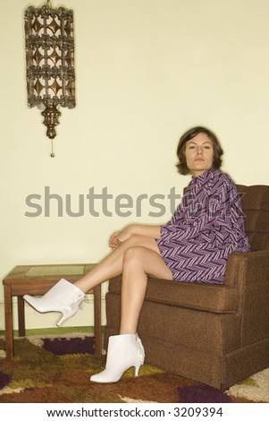 Pretty Caucasian mid-adult woman wearing vintage clothing sitting in brown retro chair looking bored. - stock photo