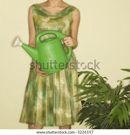 Pretty Caucasian mid-adult woman wearing vintage dress standing next to houseplant holding green watering can. - stock photo