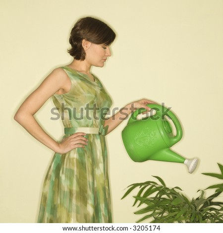 Pretty Caucasian mid-adult woman wearing vintage dress watering houseplant with green watering can. - stock photo