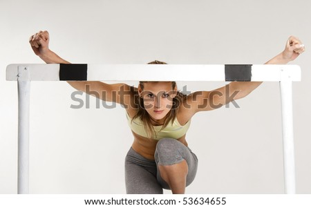 Pretty caucasian sportive model with hurdle, over gray background - stock photo