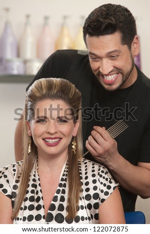 Pretty Caucasian woman and bearded hair stylist smiling - stock photo