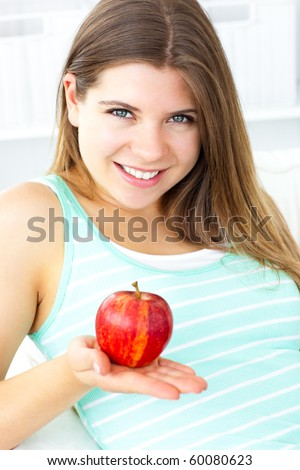Pretty caucasian woman holding an apple sitting on a sofa at home