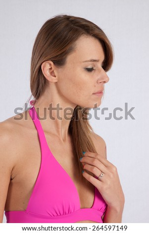 Pretty Caucasian woman in a pink swim suit, looking thoughtful - stock photo