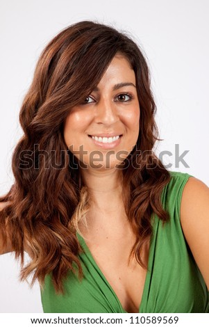 Pretty Caucasian woman in green dress,   looking at the camera with a smile, her long brunette hair falling around her face - stock photo