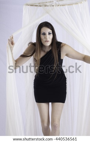 Pretty Caucasian woman in little black dress, standing behind and opening a sheer curtain