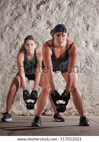 Pretty Caucasian woman lift kettle bell weights with both hands - stock photo