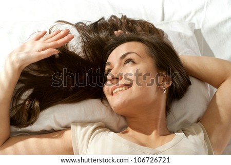 Pretty Caucasian woman lying on a pillow on a light background - stock photo