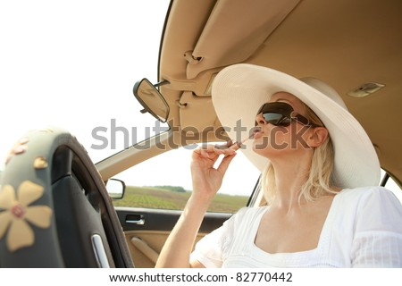 Pretty caucasian woman putting lipstick on using the car mirror - stock photo