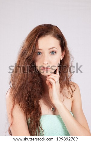 Pretty Caucasian woman with her chin on her hand and  looking  thoughtfully lat the camera