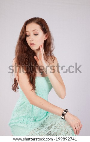 Pretty Caucasian woman with her chin on her hand and  looking  thoughtfully left - stock photo