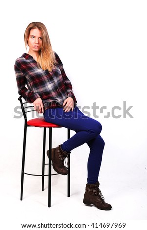 pretty charming girl Caucasian blonde in a plaid shirt and blue pants sitting on a bar stool imposingly - stock photo