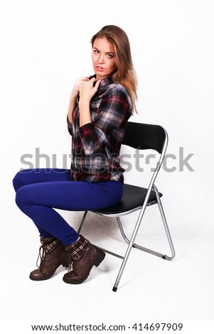 pretty charming girl Caucasian blonde in a plaid shirt and blue pants sitting on a chair, closing collar and chest by hands, modest, isolated on white - stock photo