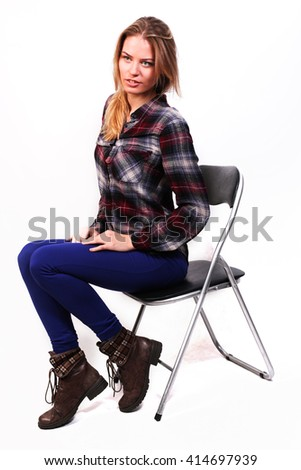 pretty charming girl Caucasian blonde in a plaid shirt and blue pants sitting on a chair, humble, isolated on white - stock photo