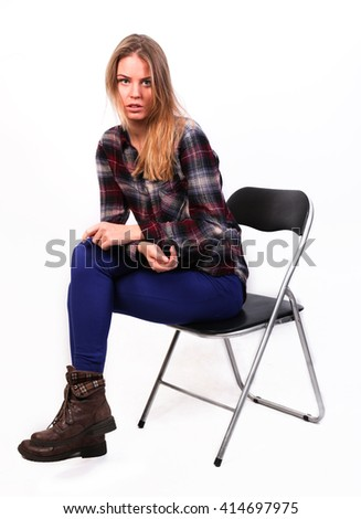 pretty charming girl Caucasian blonde in a plaid shirt and blue pants sitting on a chair, isolated on white - stock photo