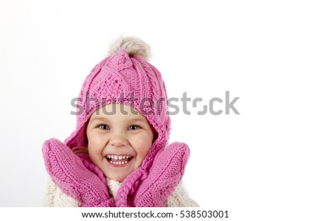 Pretty charming little girl in a knitted hat and a mittens. sHe is smiling  laughs and looking up. close-up portrait
