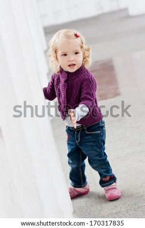Pretty charming toddler girl playing hidden behind the white columns - stock photo