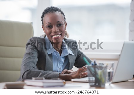 Pretty cheerful african businesswoman working with laptop in office and looking at camera - stock photo