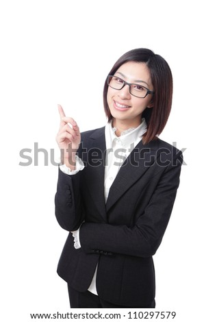 Pretty cheerful business woman pointing at something in the air with her index finger. White background, asian girl - stock photo