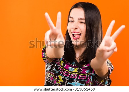 Pretty cheerful girl, with straight dark hair, wearing on colorful shirt, have fun on the orange background, in studio, waist up - stock photo