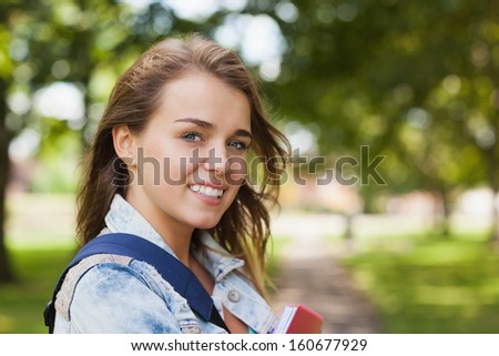 Pretty cheerful student holding folder and notebook on campus at college - stock photo