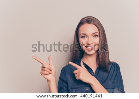 Pretty cheerful woman gesturing with fingers and showing away - stock photo
