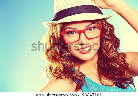 Pretty cheerful woman in hat and glasses smiling at the camera.  - stock photo