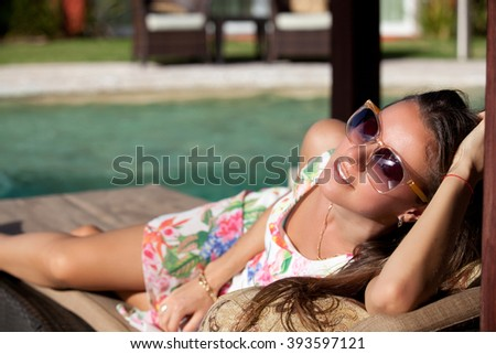 Pretty cheerful woman, relaxing at the luxury poolside. Girl at travel spa resort pool. Summer luxury vacation. (focus on woman face) - stock photo