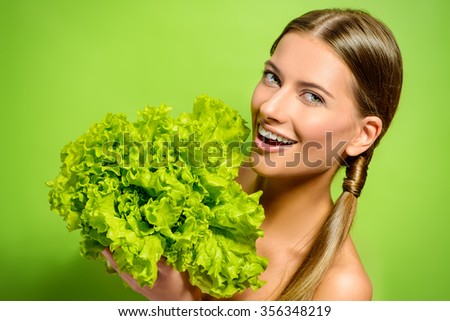 Pretty cheerful young woman posing with fresh green lettuce leaves. Healthy eating concept. Dieting. - stock photo