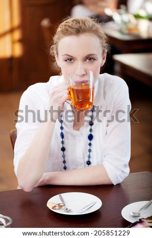 Pretty chic young woman drinking tea in a glass mug in a restaurant seated at a table facing the camera
