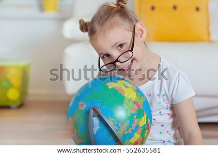 Pretty child girl at home dreaming of travel and tourism, exploring the world map and globe