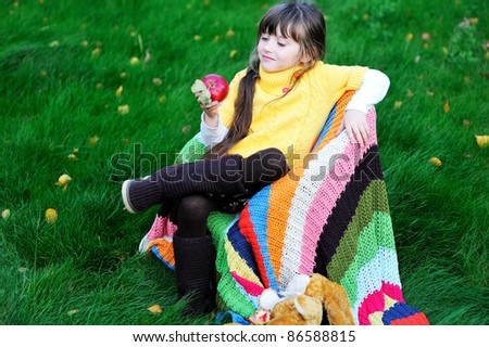 Pretty child girl eats red apple sitting in a chair outdoors - stock photo
