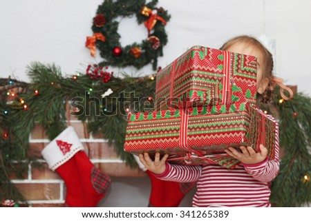 Pretty child girl holding some packed gifts in such way that her face is not seen, near Christmas decorated fireplace, winter holiday family concept - stock photo