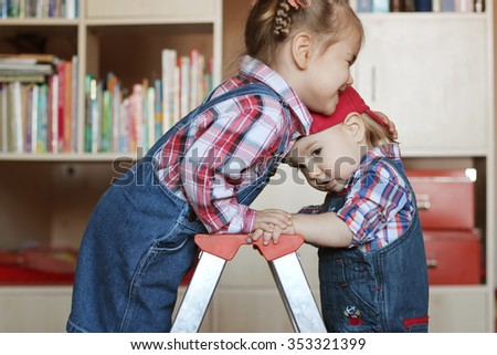 Pretty child girl hugging with inspiration her little toddler brother, both wearing in jeans overalls and standing on the step ladder, indoor building concept - stock photo