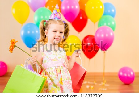 pretty child girl with gifts and flower on birthday party