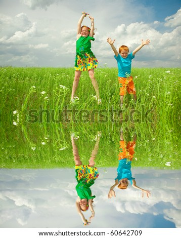 Pretty child having fun in the field. Specular reflection in the water. - stock photo