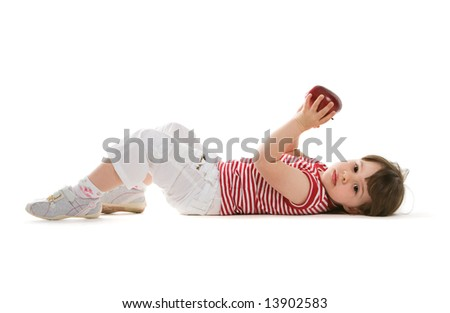 Pretty child lying on the floor with a red apple in hand - stock photo