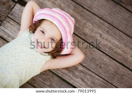 Pretty child lying on wooden surface. - stock photo