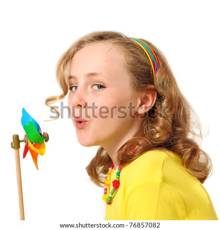 pretty child showing energy saving concept blowing windmill - stock photo