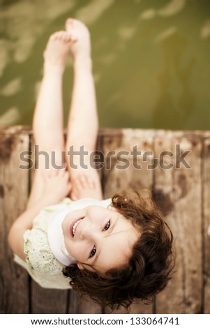 Pretty child sitting on wooden surface. - stock photo