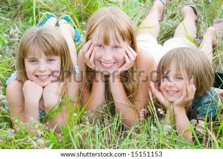 Pretty children and teenager girls on green summer grass - stock photo