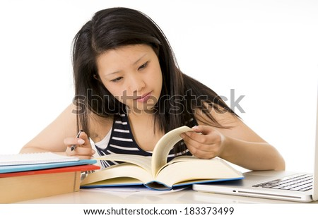 pretty chinese asian woman reading and studying on her laptop on a white background