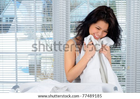 Pretty Chinese Girl With Long Hair Doing Laundry At Home - stock photo