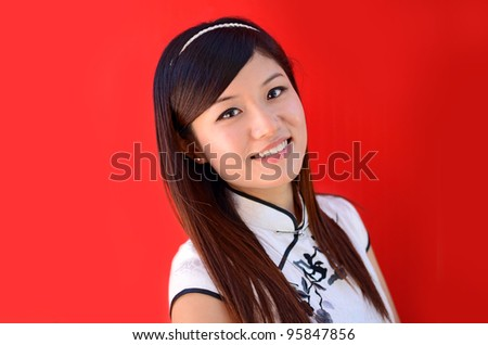 Pretty chinese woman in traditional cheongsam over red background - stock photo