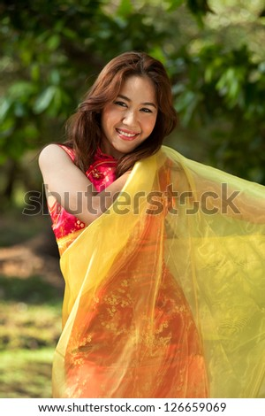 Pretty Chinese  woman in  traditional dress in a cheerful manner.
