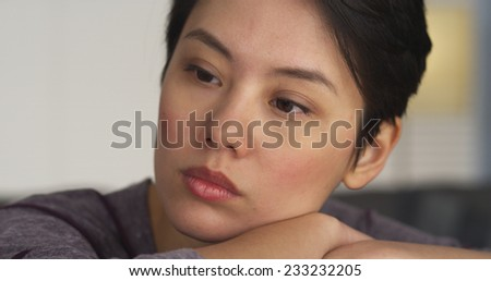 Pretty Chinese woman thinking on desk - stock photo