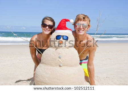 Pretty Christmas couple having fun at beach with perfectly build snowman made out of sand. With sunglasses, carrot nose and shells as buttons and mouth and santa hat. - stock photo