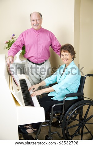 Pretty church pianist in wheelchair, playing piano while a singer turns pages for her.